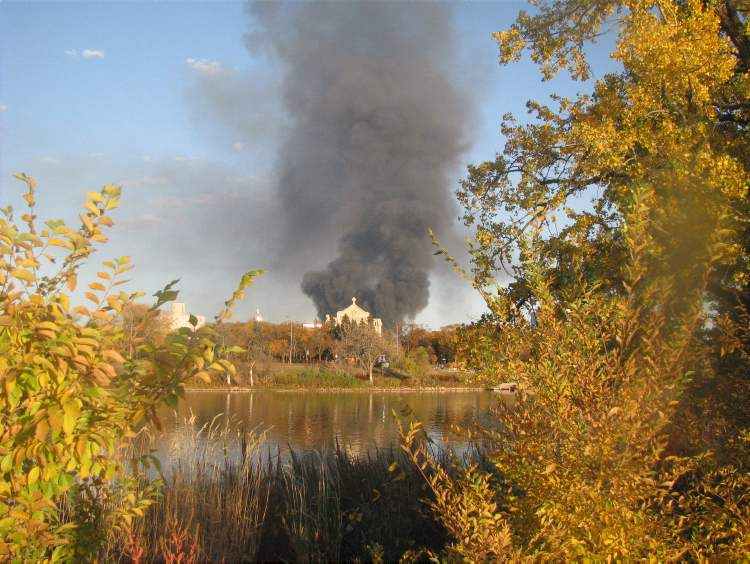 The fire is seen from across the Red River, behind the St. Boniface Cathedral. (Luc Labelle / Submitted photo)