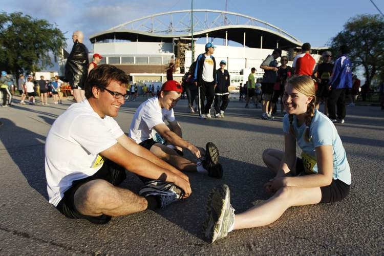 Half-marathoners Brayden Lacrois, Sean Rohringer and Ingrid Baragar stretch before the race.  (TREVOR HAGAN / WINNIPEG FREE PRESS)