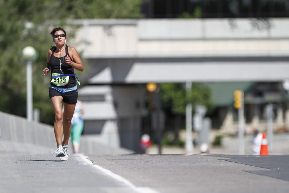 A runner pushes on towards the Mile 18 marker on Queen Elizabeth Way. (JESSICA BURTNICK/WINNIPEG FREE PRESS)