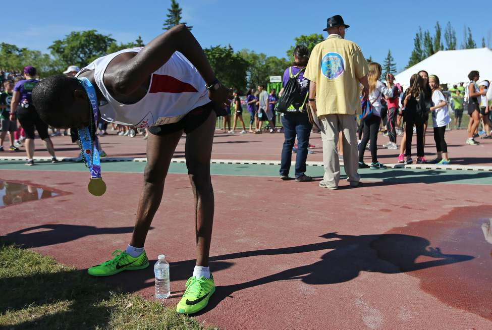 Evans Maiko, of Kenya, marathon winner, catching his breath shortly after crossing the finish line. (TREVOR HAGAN/WINNIPEG FREE PRESS)