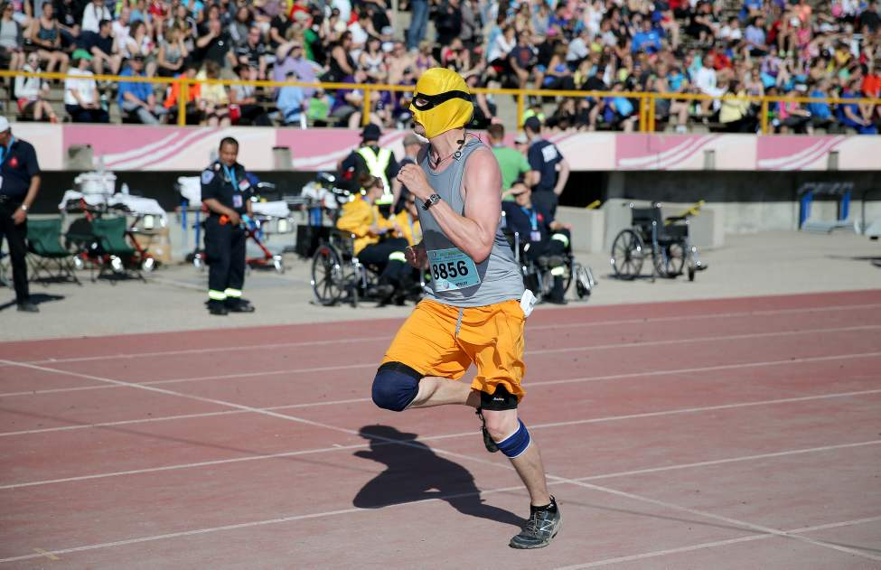 A masked half marathon participant crosses the finish line at the University of Manitoba. (TREVOR HAGAN/WINNIPEG FREE PRESS)