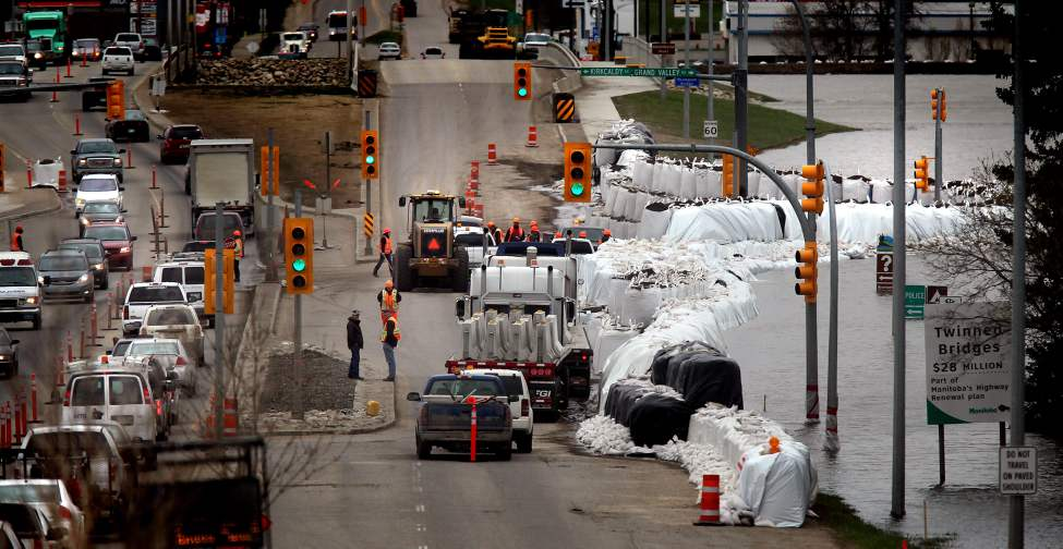 "Giant ""superbags"" keep the swollen Assiniboine River at Bay in Brandon's Assiniboine Valley at 18th Street and Kirkaldy Drive. Traffic has been reduced to two lanes and a neighboring Big Box Center was shut down to reduce traffic alongside the dike. The only other major route across the valley , First Street, has been shut down leaving 18th the only north south route open. May 12, 2011. (Phil Hossack / Winnipeg Free Press)"