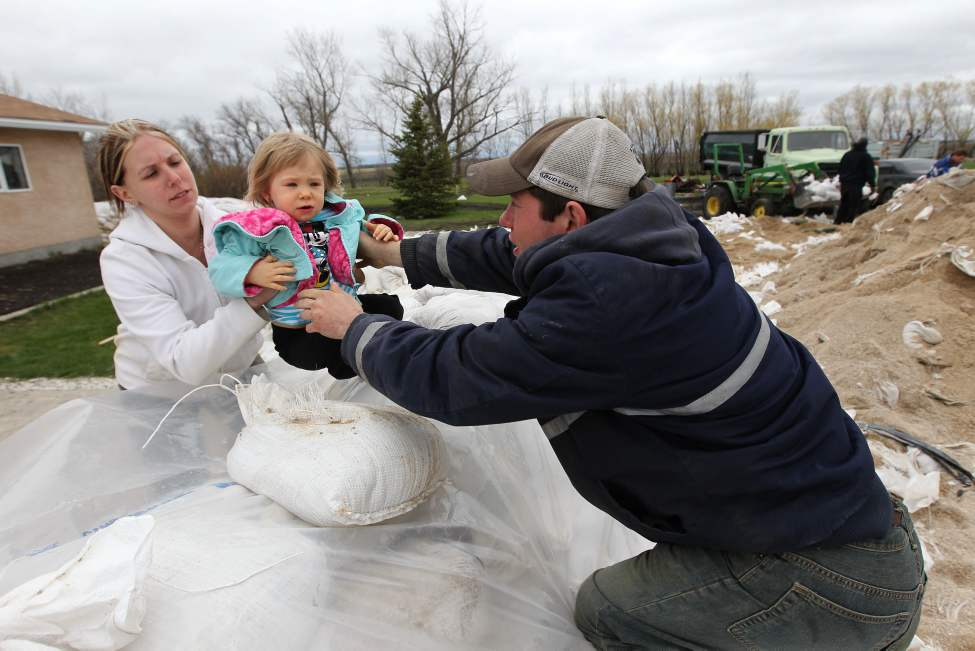 Matt Janzen reaches across his 5ft dike to hand his 2 year old daughter Kaitlyn to his wife Melanie at outside their home just outside Elie Manitoba Thursday.  The family have a one of the lowest homes in the community and will have to leave the dike in place and for a min of 6 weeks.  May 12, 2011. (Ruth Bonneville / Winnipeg Free Press)