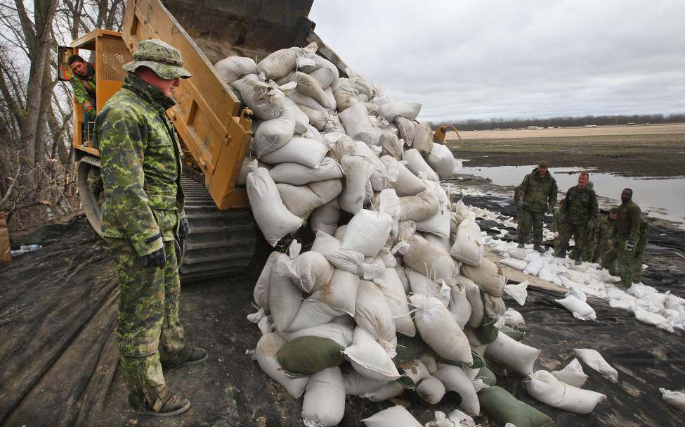 Members of 2 PPCLI  Shilo reinforce a dike on the Assinboine River off Hyw 430, north of  Oakville, MB Thursday. A soldier drives on a 8 wheel off road vehicle.  May 12, 2011. (Joe Bryksa / Winnipeg Free Press)
