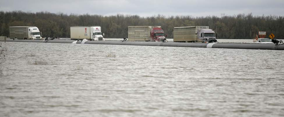 A line of semi-trucks are escorted by a pilot vehicle along the Eastern Access Route near Victoria Avenue East on Thursday. A single lane of traffic has been opened up to allow truck traffic around the eastern side of Brandon, Manitoba.  May 12, 2011 (Bruce Bumstead/Brandon Sun)
