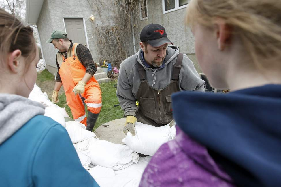 Volunteers sandbag at Dr. Robin Carters house. He lives about 600 yards from where the cut will happen. Elm Creek runs right next door to his house. May 12, 2011. (Trevor Hagan / Winnipeg Free Press)