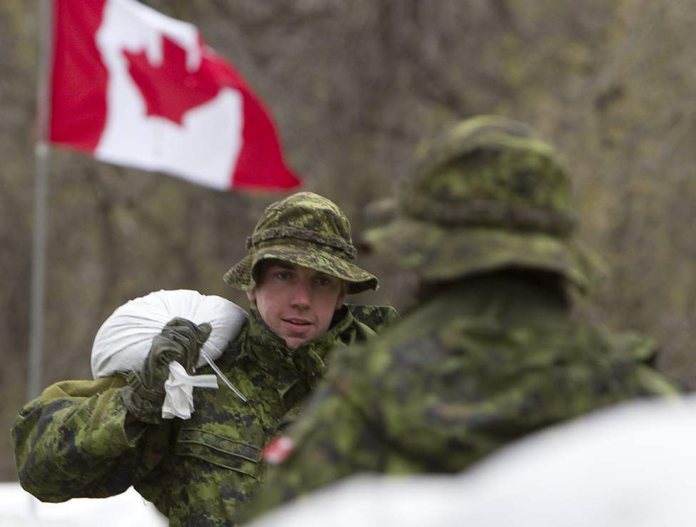Members of the Canadian Forces carry sandbags to a home located close to the Hoop and Holler Bend near Portage La Prairie, Man, Thursday, May 12, 2011. (THE CANADIAN PRESS/Jonathan Hayward)