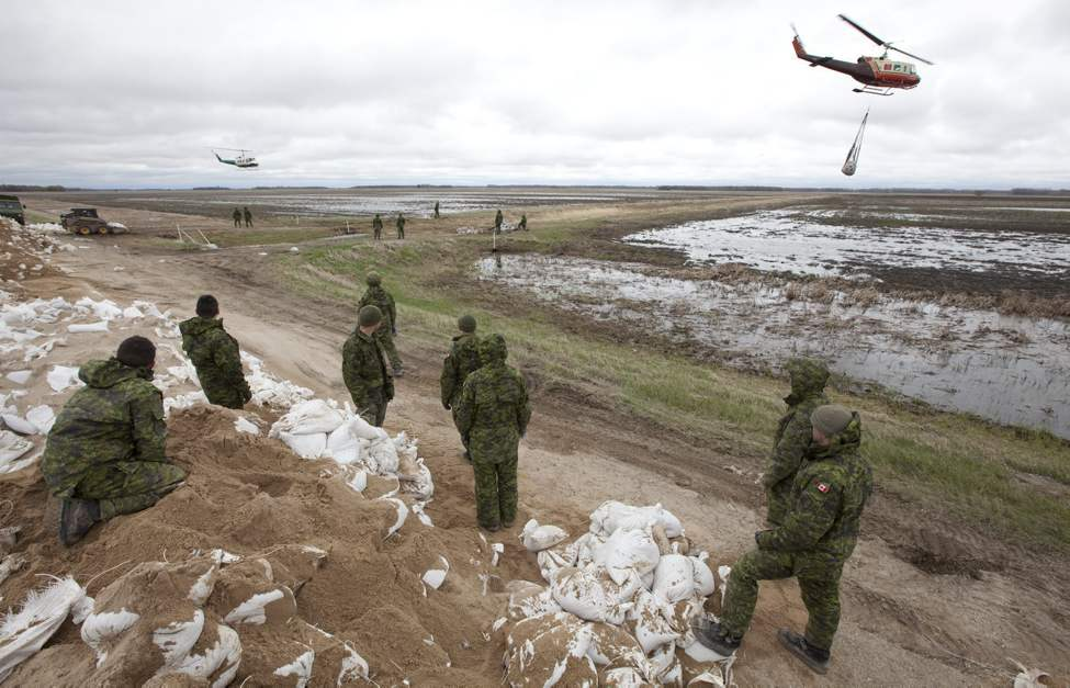 Members of 2nd battalion Princess Patricia's Light Infantry help load sandbags onto helicopter slings to be transported to weak sections of the dike running along the Assiniboine River some 25km from Portage La Prairie, Man. Thursday, May 12, 2011.(THE CANADIAN PRESS/Jonathan Hayward)