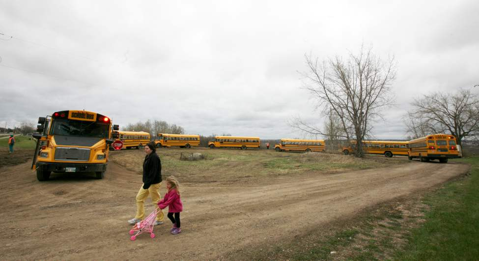 Students displaced from Kirkcaldy Heights School in Brandon, closed as it's in the flood evacuation zone, board a convoy of buses at a temporary loading zone on Braecrest Drive in north Brandon Friday morning. The school is temporarily holding classes at Brandon University. May 13, 2011 (James O'Connor/Brandon Sun)