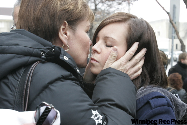 Carol deDelley (left) mother of Tim McLean, kisses her daughter Katie outside the Law Courts in Winnipeg Thursday.