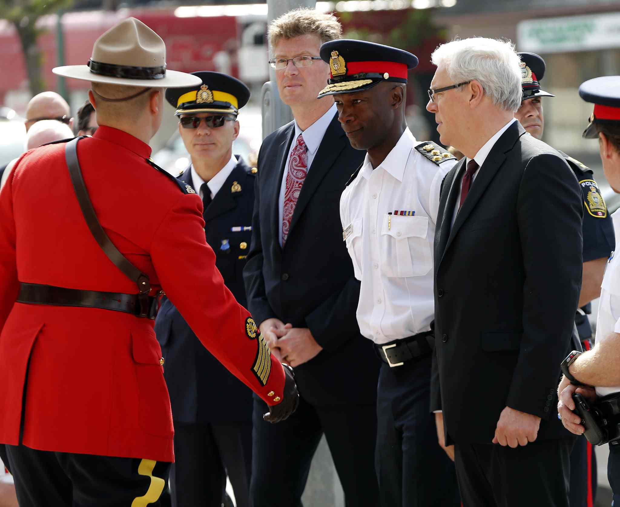 A wreath-laying ceremony on Portage Avenue Tuesday allowed Manitoba's RCMP D Division to honour the three Moncton officers who died following a shootout last week. The ceremony included Attorney General Andrew Swan, left, Winnipeg Police Chief Devon Clunis, centre, and Premier Greg Selinger.