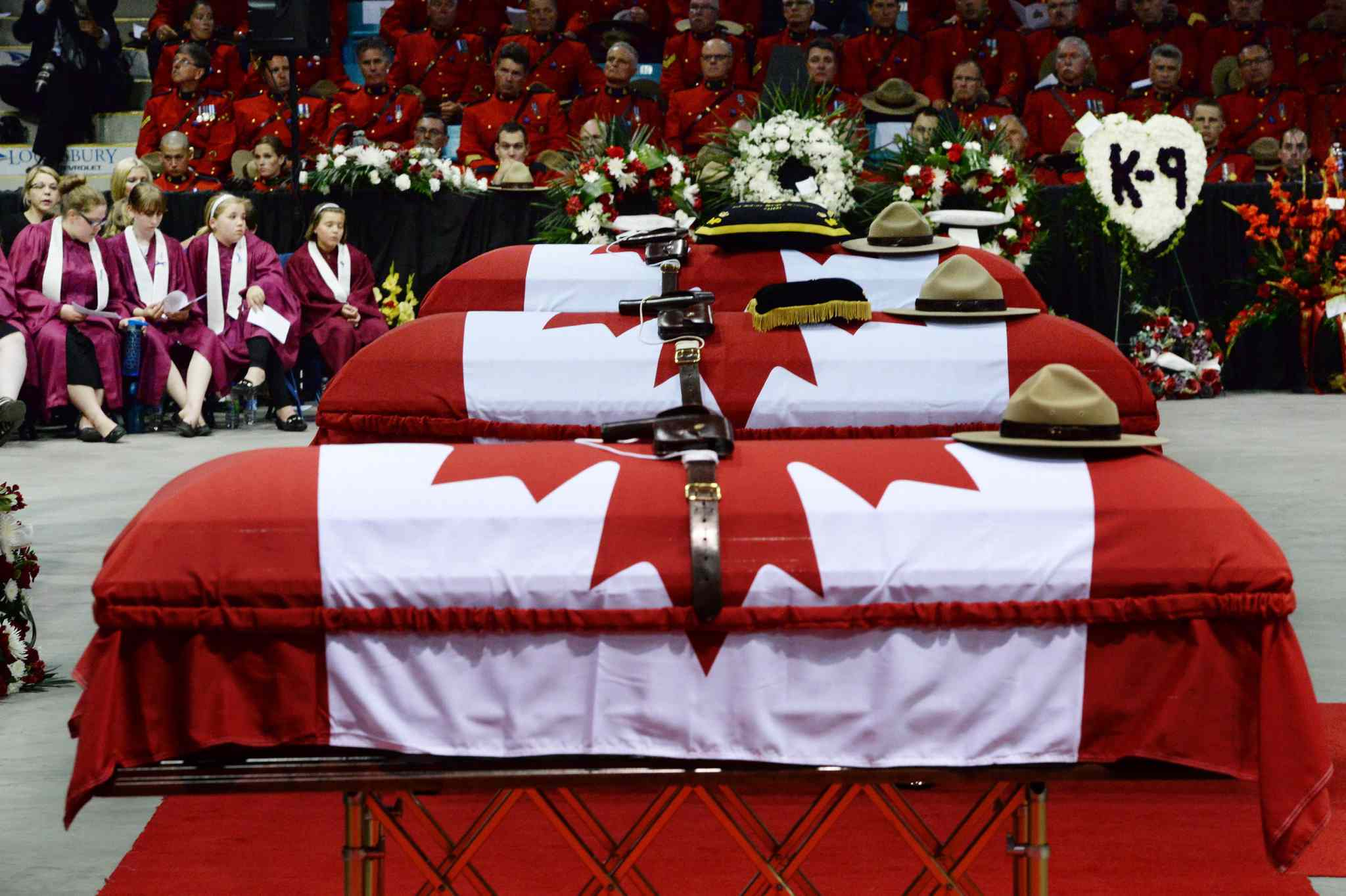 Stetsons rest on the caskets of the three slain RCMP officers, Const Dave Ross, Const. Douglas Larche and Const. Fabrice Gevaudan.