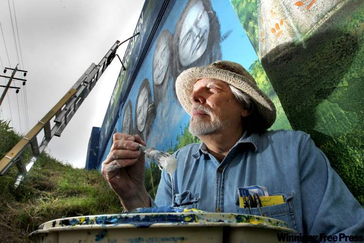 Artist Tom Andrich next to his latest mural on the Empress Street overpass, of missing and murdered Aboriginal women.