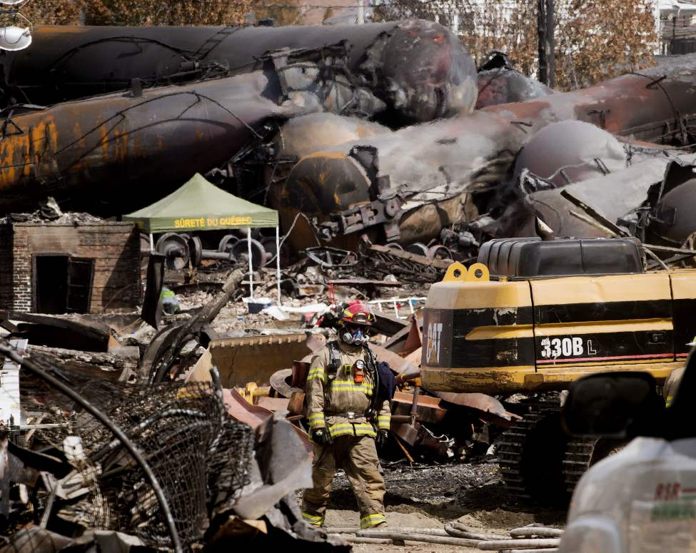 A fireman walks through the debris as work continues at the crash site of the train derailment and fire Tuesday, July 16, 2013 in Lac-Megantic, Que. that left 37 people confirmed dead and another 13 missing and presumed dead.THE CANADIAN PRESS/Ryan Remiorz (CP)