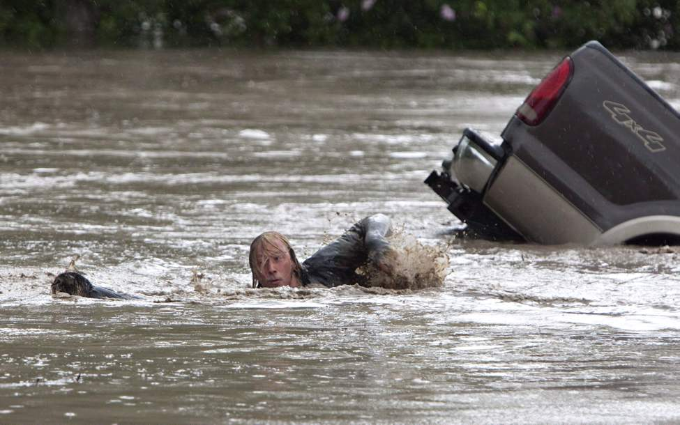 Kevan Yeats swims after his cat Momo to safety in High River, Alta. on June 20, 2013. Yeats who gained international fame after leaping from a submerged pickup truck into Alberta floodwaters says he was surprised at how eagerly the feline took to the rushing water. THE CANADIAN PRESS/Jordan Verlage (CP)