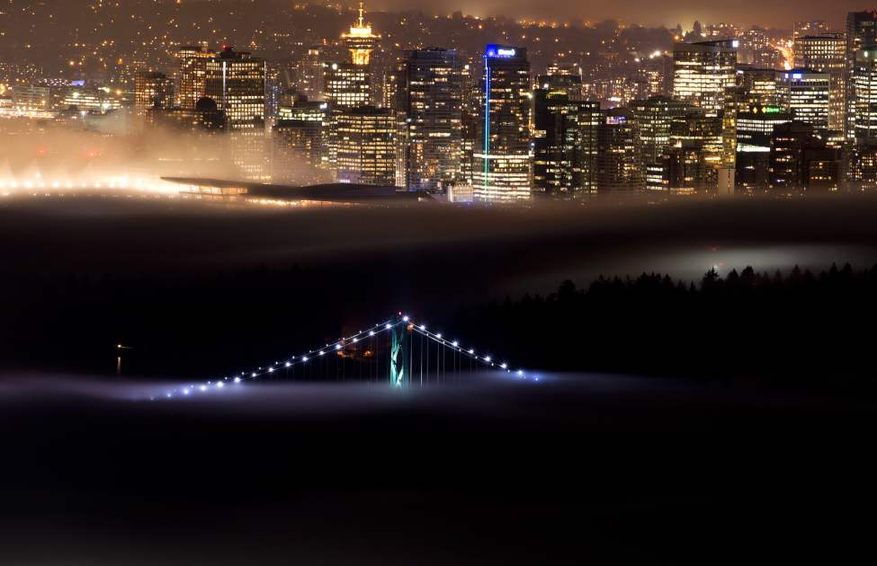 A small tip of the Lions Gate Bridge sticks out of the fog rolling into Vancouver harbour late Thursday night, Oct. 24, 2013. A weather system has brought heavy fog into Vancouver and the lower mainland for more than a week. THE CANADIAN PRESS/Jonathan Hayward (CP)