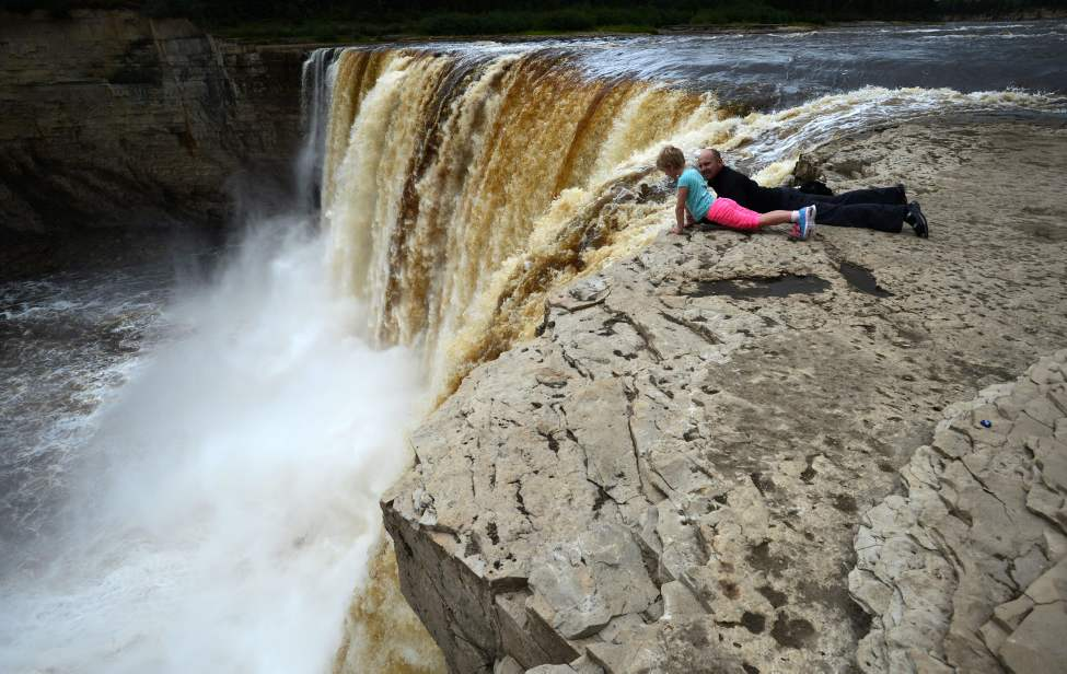 Stephane Sevigny keeps an eye on his daughter Serena, 7, of Yellowknife as they lie down to get a view of Alexandra Falls on the Hay River south of Hay River, Northwest Territories on Tuesday, August 20, 2013. THE CANADIAN PRESS/Sean Kilpatrick (CP)