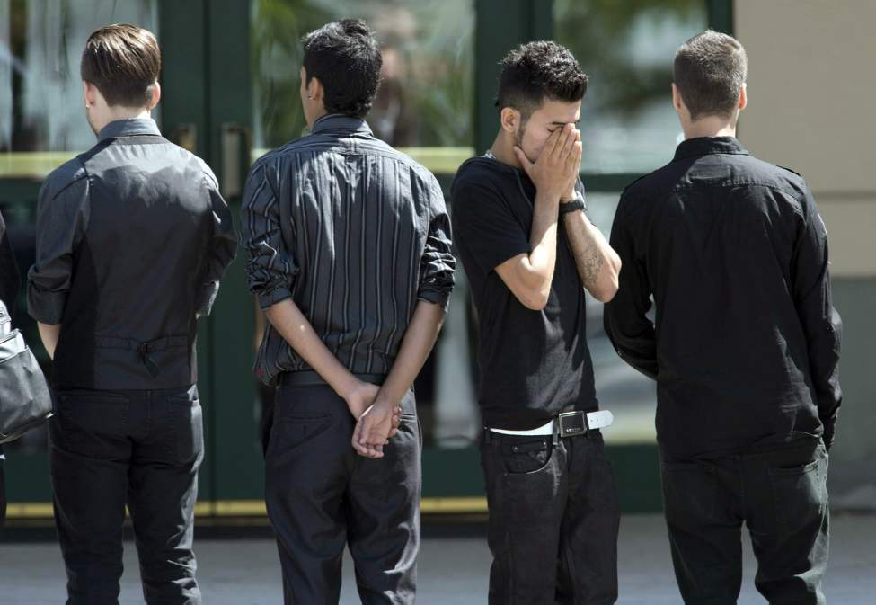 "Mourners react outside the funeral for 18-year-old Sammy Yatim in Toronto, Thursday, Aug.1, 2013. Yatim died Saturday morning after receiving multiple gunshot wounds during an ""interaction"" with police. THE CANADIAN PRESS/Frank Gunn (CP)"