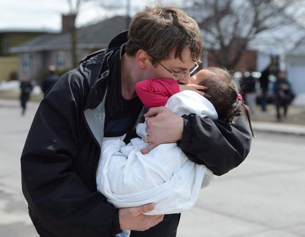 A child is hugged after police release the children to family at the scene of a shooting in Gatineau on Friday April 5, 2013. THE CANADIAN PRESS/Sean Kilpatrick (CP)