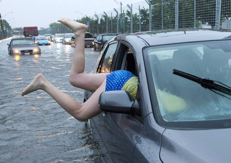 A woman gets back into her flooded car on the Toronto Indy course on Lakeshore Boulevard in Toronto on Monday, July 8 2013. THE CANADIAN PRESS (CP)