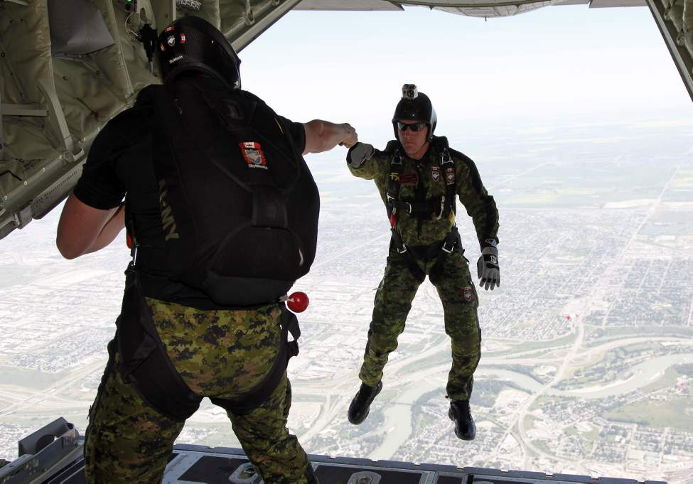 Cpl Mathieu Lebel, from Quebec City, Que., of the Canadian Forces Skyhawks parachute team jumps out of a Hercules aircraft deploy over the Calgary Stampede rodeo in Calgary, Alta., Thursday, July 11, 2013. THE CANADIAN PRESS/Jeff McIntosh (CP)