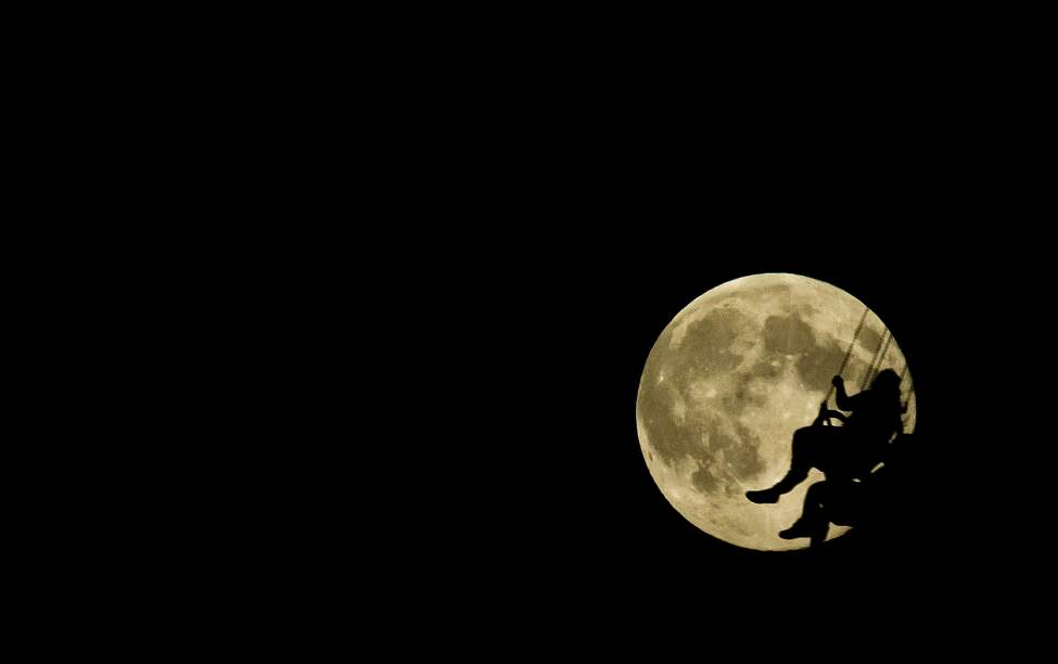 A fair-goer is silhouetted against a blue moon while riding the