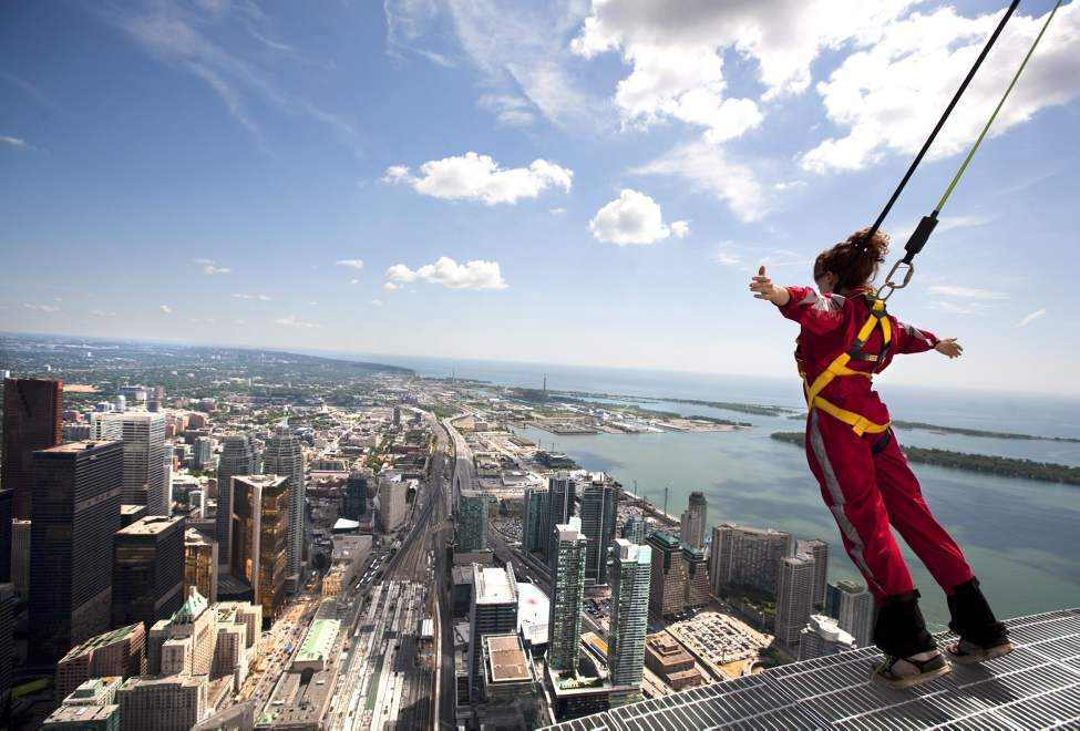 Canadian Press reporter Alexandra Posadzki leans over Toronto's downtown while participating in a media preview of EdgeWalk on the CN Tower Wednesday, July 27, 2011. Participants are strapped in to a harness as they walk along a walkway around the CN Tower. THE CANADIAN PRESS/Darren Calabrese