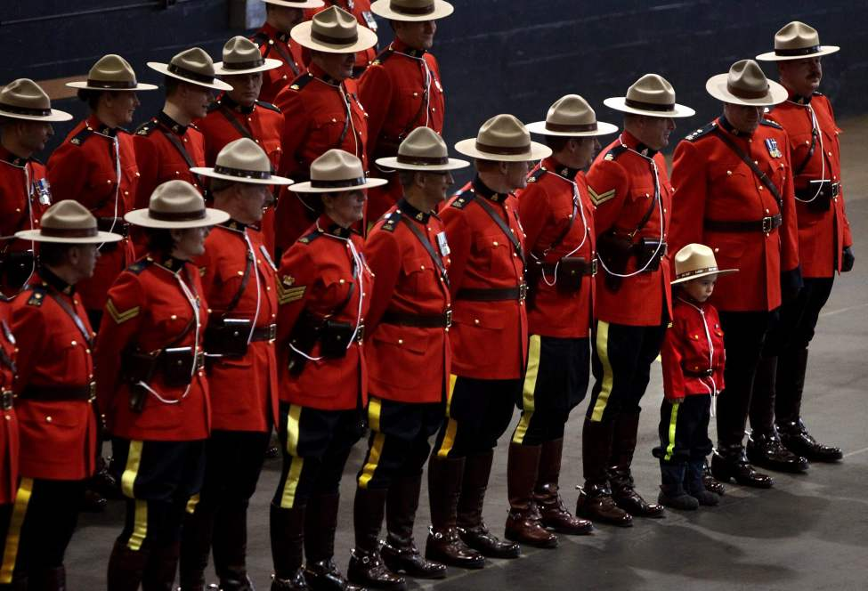 "Four-year-old Jack Robertson wears the Red Serge as he stands with RCMP officers during an RCMP change of command ceremony in Vancouver, B.C., on Friday February 11, 2011. Command of the RCMP's ""E"" Division was transferred to Assistant Commissioner Peter Hourihan from Deputy Commissioner Gary Bass who has assumed the role of Deputy Commissioner West, overseeing RCMP operations in western Canada. THE CANADIAN PRESS/Darryl Dyck"