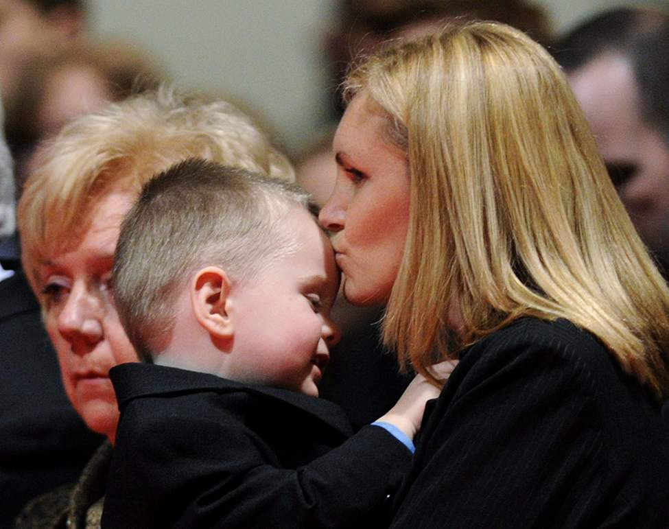 Christine Russell, right kisses her two-year-old son Nolan Russell's head as they attend the funeral for Toronto Police Sgt. Ryan Russell in Toronto on Tuesday, January 18, 2011. Thousands honoured Sgt. Russell after being killed by a stole snow plow on January 12 in Toronto. THE CANADIAN PRESS/Nathan Denette