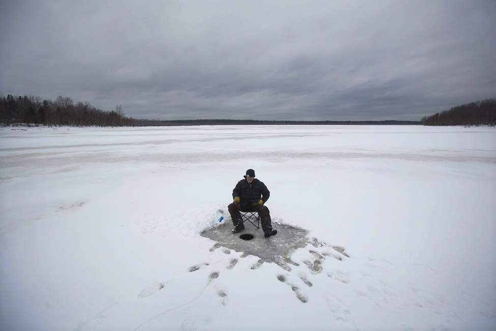 A man ice fishes on French Lake near Fredericton, N.B. on Tuesday, January 18, 2011. THE CANADIAN PRESS/Darren Calabrese