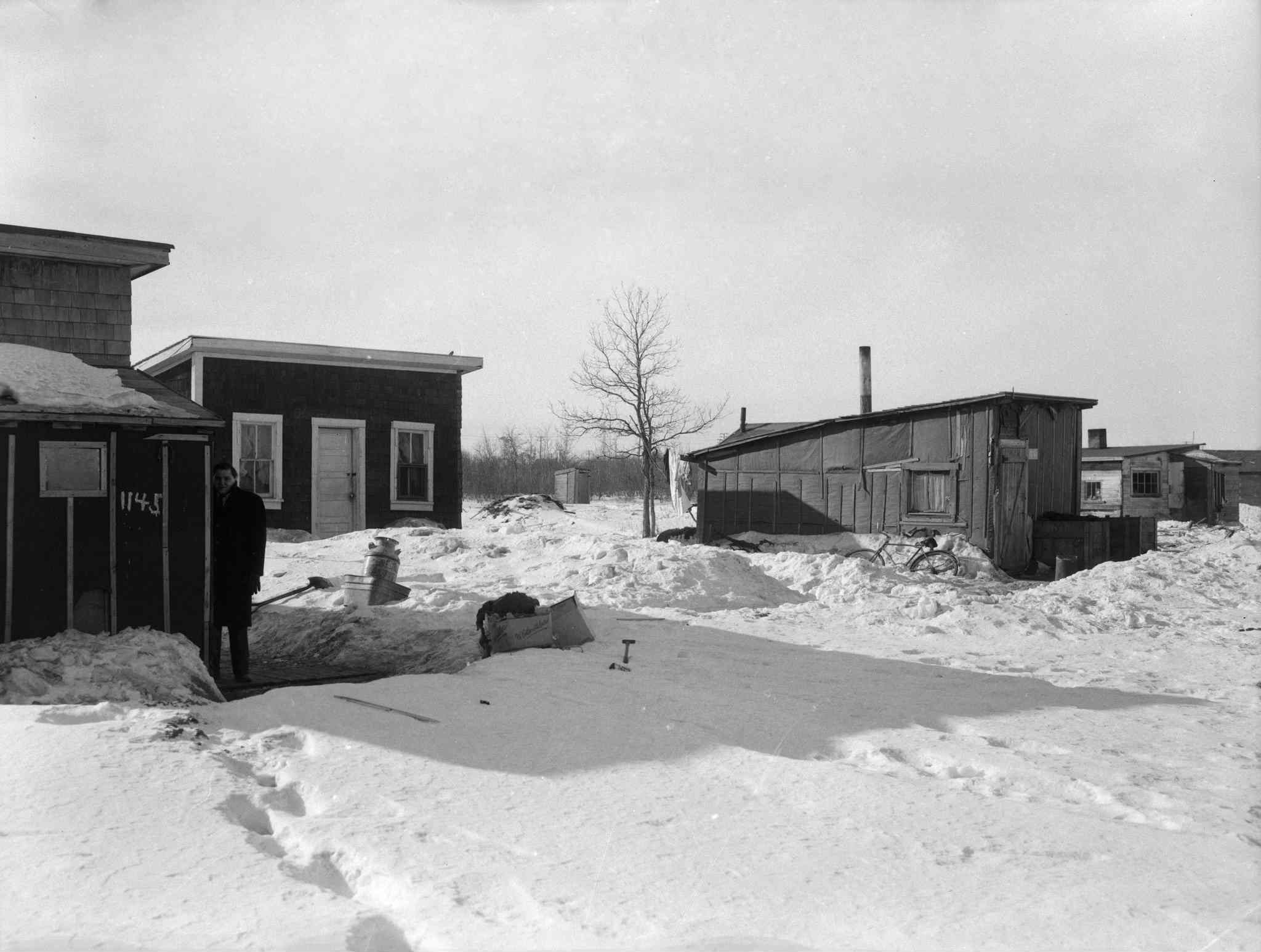 A news reporter stands outside the home of James and Mary Parisien at 1145 Weatherdon Avenue in 1959. Despite their simple construction, the shanties displayed some variations in status. The wooden shingle siding of the Parisien residence distinguishes it from the tar-paper cladding of some of its neighbours. Beside 1145 Weatherdon is a home with painted trim and sashes.