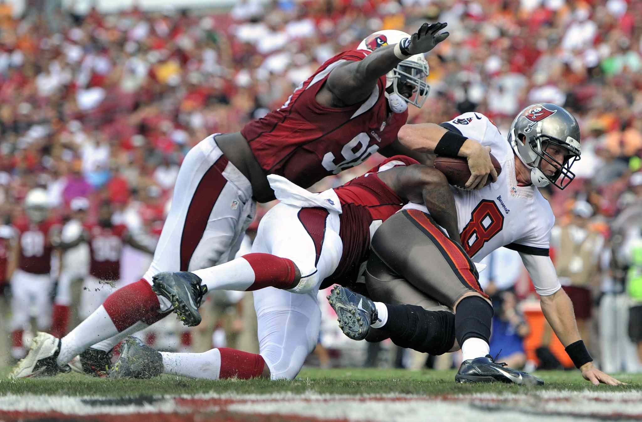 Tampa Bay Buccaneers quarterback Mike Glennon (right) is sacked by Arizona Cardinals Dontay Moch and Frostee Rucker (left) during Arizona's 13-10 win Sunday in Tampa, Fla.