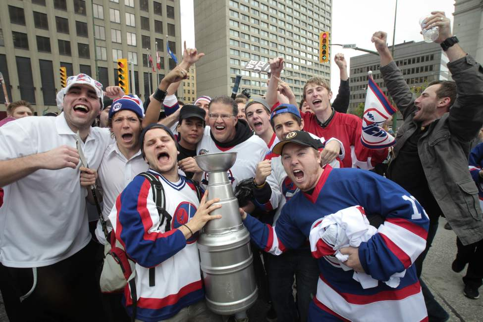 Hockey fans gathered at Portage and Main to celebrate the return of the NHL to Winnipeg, MB. Fans cheer as Dancing Gabe arrives at Portage and Main. (MIKE DEAL / WINNIPEG FREE PRESS)
