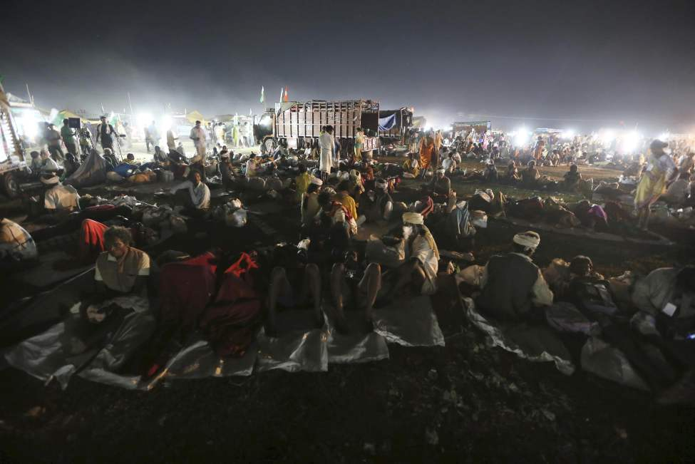 Rural Indians, including landless farmers, rest during an overnight halt of the