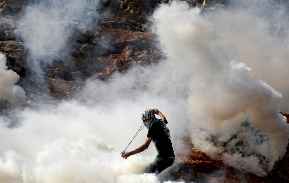 A masked Palestinian protester hurls back a tear gas canister shot by Israeli soldiers, unseen, during clashes outside the Ofer military prison, near the West Bank city of Ramallah, Wednesday, Oct. 10, 2012. The clashes started during a demonstration calling to release prisoners jailed in Israel. (AP Photo/Majdi Mohammed)