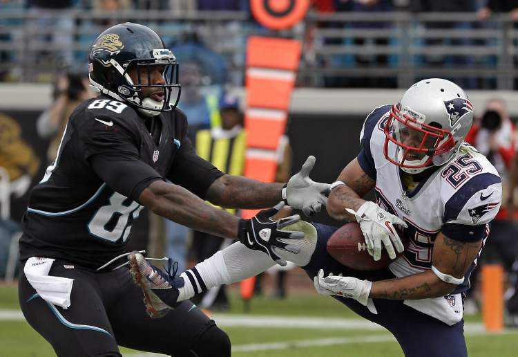 New England Patriots free safety Patrick Chung, right, intercepts a pass in front of Jacksonville Jaguars tight end Marcedes Lewis (89) as time expires in an NFL football game on Sunday, New England won the game 23-16. (CP)