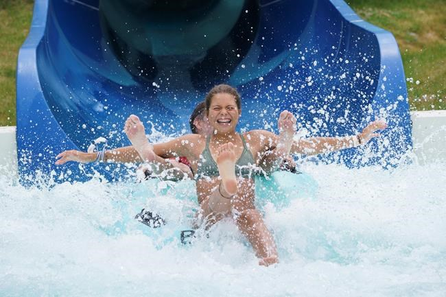 Swimmers splash down a water slide in Bromont, Que. on Monday, June 29, 2020 as water parks reopen in the province of Quebec. THE CANADIAN PRESS/Paul Chiasson