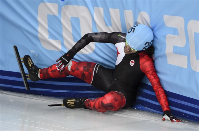 Canada's Charles Hamelin crashes into the boards on the final lap of the men's 500 metre heats at the Sochi Winter Olympics Tuesday, February 18, 2014 in Sochi. THE CANADIAN PRESS/Paul Chiasson