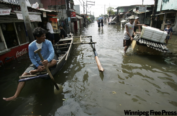 Locals float down their flooded streets offering rides at San Roque village, in Laguna province, 40 kilometres south of Manila, Philippines, today. A new typhoon gathered strength Thursday off the Philippines while nearly 700,000 people still sought help in badly stretched relief centers from massive flooding caused by Ketsana, one of the region's most destructive storms in years.