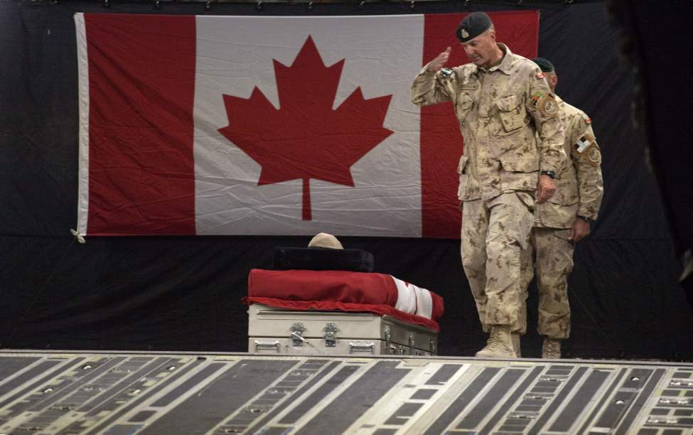 Brig.-Gen Dean Milner, Commander of Canadian forces in Afghanistan, salutes the casket of Master Cpl. Francis Roy, a member of the Army's special forces regiment, during a ramp ceremony aboard an aircraft in the early hours Tuesday, June 28, 2011 at Afghanistan's Kandahar Airfield. Roy was found mortally wounded by fellow soldiers early Saturday at a forward operating base in Kandahar city. His death is still under investigation by military police, but enemy action has been ruled out. (AP Photo/David Goldman)