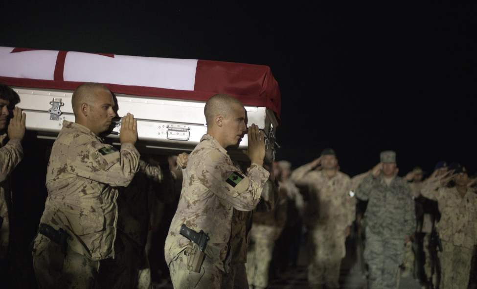 Soldiers carry the casket of Master Cpl. Francis Roy, a member of the Canadian Army's special forces regiment, to a waiting aircraft during a ramp ceremony in the early hours Tuesday, June 28, 2011 at Afghanistan's Kandahar Airfield. Roy was found mortally wounded by fellow soldiers early Saturday at a forward operating base in Kandahar city. His death is still under investigation by military police, but enemy action has been ruled out. (AP Photo/David Goldman)