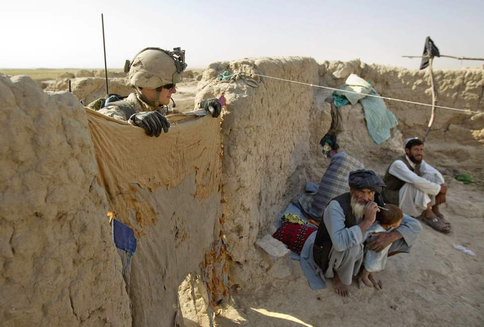 Canadian Army soldier Sgt. Marc Jorg, 23, of Quebec, Canada, with the1st Battalion Royal 22nd Regiment looks on as Abdulsalam, lower right, brushes his teeth during a search inside a compound on one of their final operations Wednesday, June 29, 2011 in the Panjwaii district of Kandahar province, Afghanistan. (AP Photo/David Goldman)
