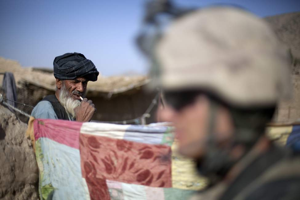 A local Afghan man who goes by the name of as Abdulsalam, left, brushes his teeth from inside his compound as soldiers with the Canadian Army's 1st Battalion Royal 22nd Regiment conduct one of their final operations Wednesday, June 29, 2011 in the Panjwaii district of Kandahar province, Afghanistan. (AP Photo/David Goldman)