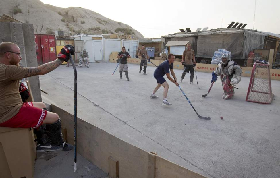 Cpl. Sebastien Richer, 35, left, of Quebec, Canada, waits to play in a game of hockey Wednesday, June 29, 2011 on Forward Operating Base Sperwan Ghar in the Panjwaii district of Kandahar province, Afghanistan. (AP Photo/David Goldman)