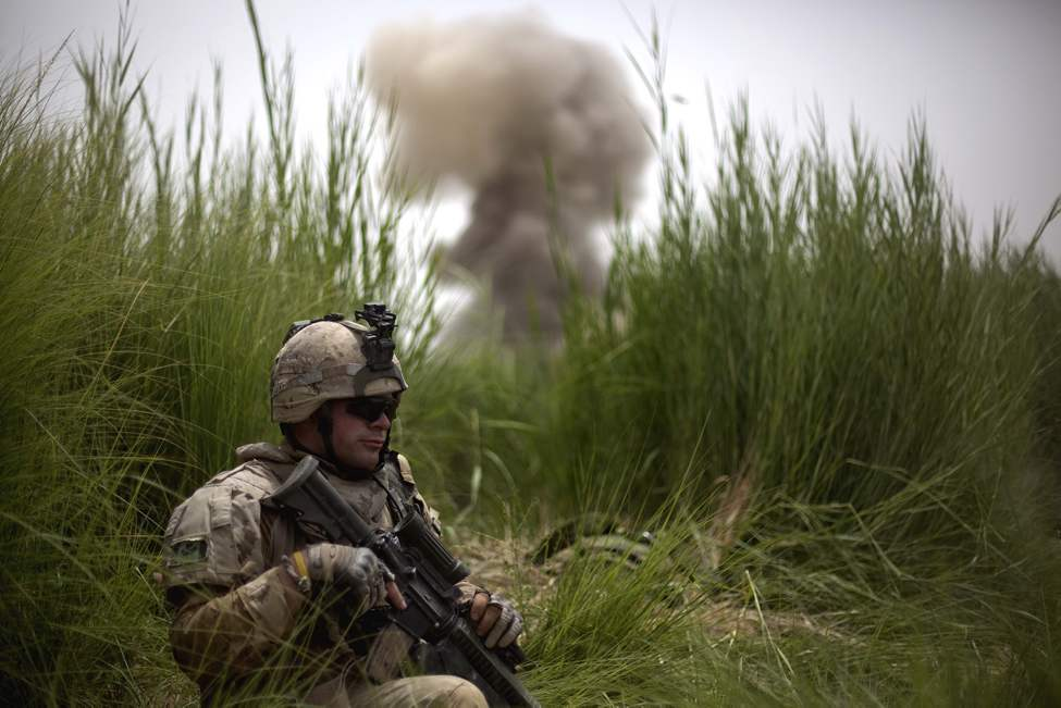 Jonathan Chalifoux, 23, of Germanville, Quebec, Canada, with the Canadian Army's 1st Battalion 22nd Royal Regiment, takes cover as a controlled detonation goes off in the background during an operation Sunday, June 26, 2011 in the Panjwaii district of Kandahar province, Afghanistan. (AP Photo/David Goldman)