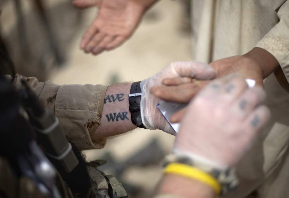A tattoo decorates the arm of Cpl. Jonathan Chalifoux, 23, of Germanville, Quebec, Canada, with the Canadian Army's 1st Battalion 22nd Royal Regiment, as he tests a teenager's hand for explosive and gun powder residue during an operation Sunday, June 26, 2011 in the Panjwaii district of Kandahar province, Afghanistan. (AP Photo/David Goldman)
