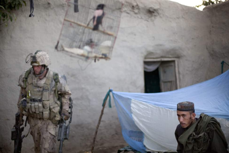 An Afghan man at right wakes up from under a sleeping tent as soldiers with the Canadian Army's 1st Battalion Royal 22nd Regiment search a compound on their final operation Thursday, June 30, 2011 in the Panjwaii district of Kandahar province, Afghanistan. (AP Photo/David Goldman)
