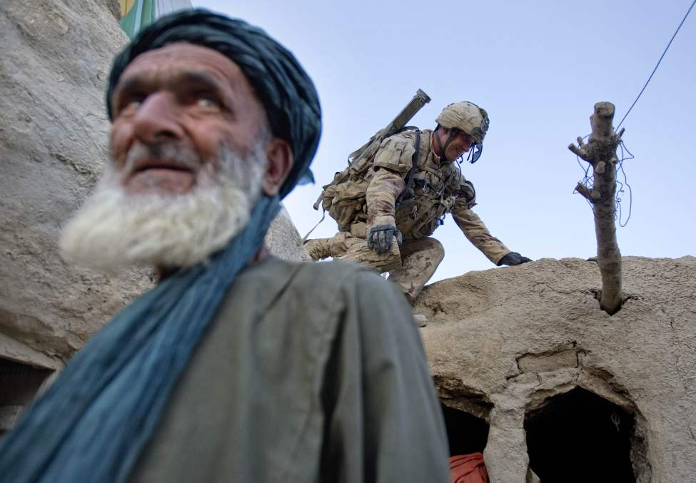 Pvt. Richard Boutet, 38, of Quebec City, Canada, background with the Canadian Army's 1st Battalion Royal 22nd Regiment searches a compound as the owner Fazel Mohammad, left, looks on during their final operation Thursday, June 30, 2011 in the Panjwaii district of Kandahar province, Afghanistan. (AP Photo/David Goldman)