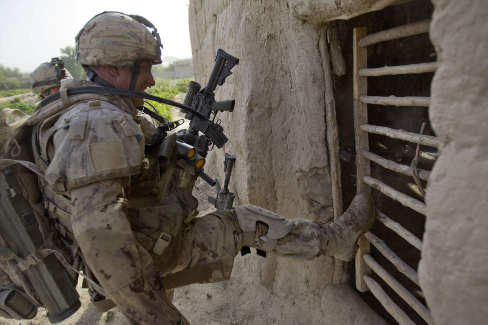 Pvt. Richard Boutet, 38, of Quebec City, Canada, with the Canadian Army's 1st Battalion Royal 22nd Regiment kicks in a door while searching a compound on their final operation Thursday, June 30, 2011 in the Panjwaii district of Kandahar province, Afghanistan. (AP Photo/David Goldman)