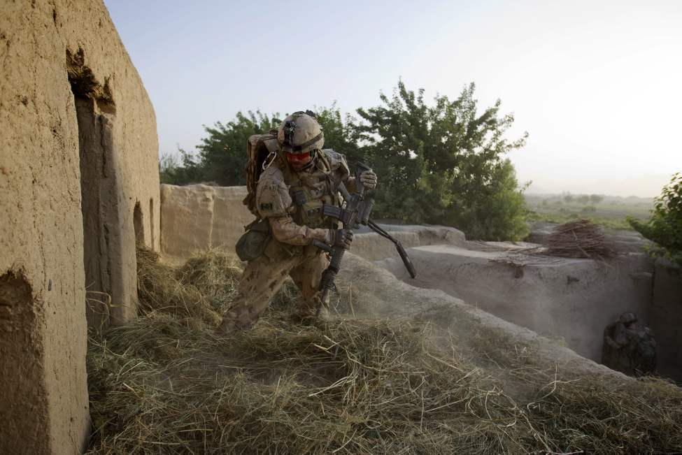 Sgt. Mathieu Pelletier, 33, of Quebec City, Canada, with the Canadian Army's 1st Battalion Royal 22nd Regiment searches a compound on their final operation Thursday, June 30, 2011 in the Panjwaii district of Kandahar province, Afghanistan. (AP Photo/David Goldman)
